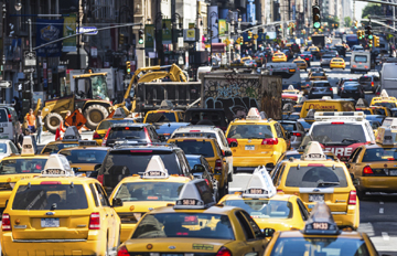 New York City, United States - May 12, 2012: Heavy traffic on busy 8th Avenue in Ney York City, USA in morning. Vast number of vehicles hit the streets and avenues of Manhattan every day. Almost half of cars are yellow taxis (well recognized city icon). Taxis are operated by private companies, licensed by the NYC Taxi Commission.